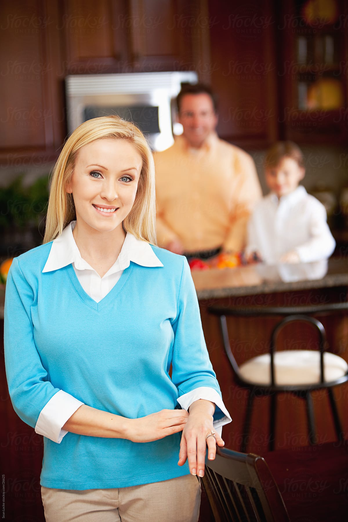 Family: Cute Mother Leans On Chair With Family In Kitchen | Stocksy ...