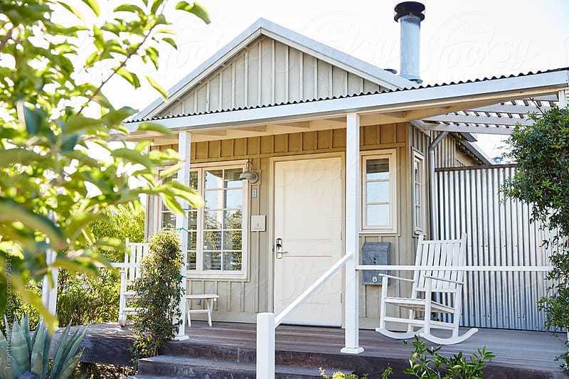 Tiny home cottage with front porch and rocking chairs by Trinette Reed for Stocksy United