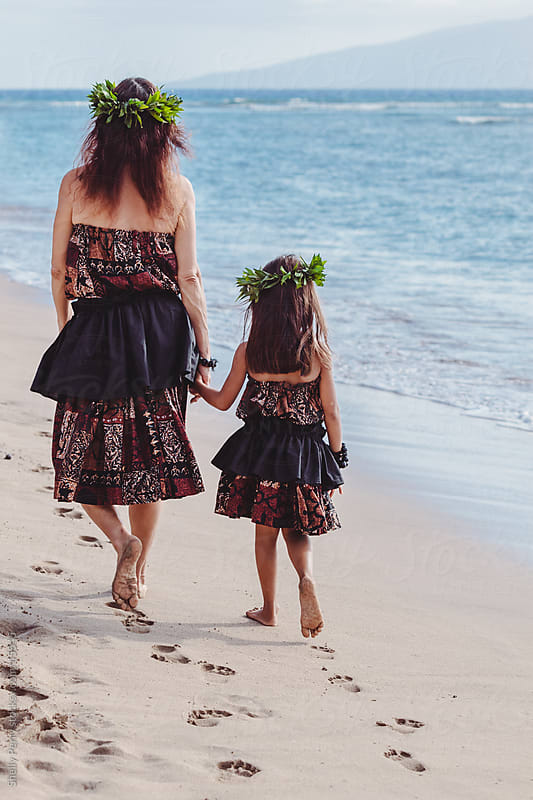 Teacher and Young Traditional Hawaiian Hula Student Walk Away Hand in Hand on the Beach by Shelly Perry for Stocksy United