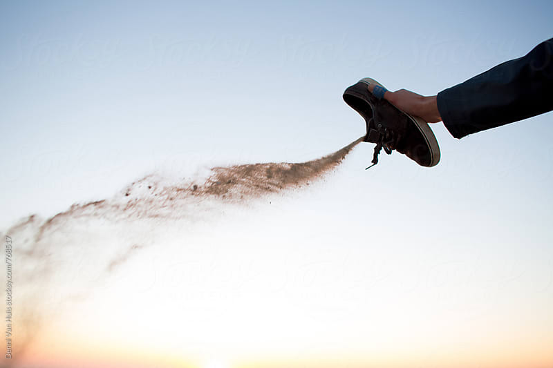 Throwing sand out of shoe on a beach during sunset by Denni Van Huis for Stocksy United