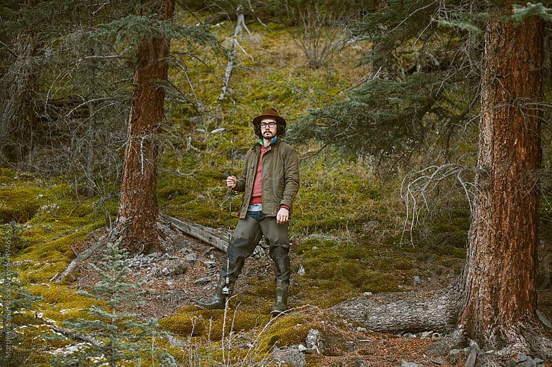 Man Standing On A Forestry Hill Holding A Fishing Pole by Matthew Smith for Stocksy United