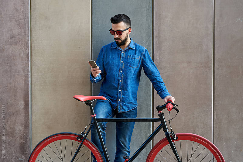 Young man on fixed gear bicycle checking his smartphone by Guille Faingold for Stocksy United
