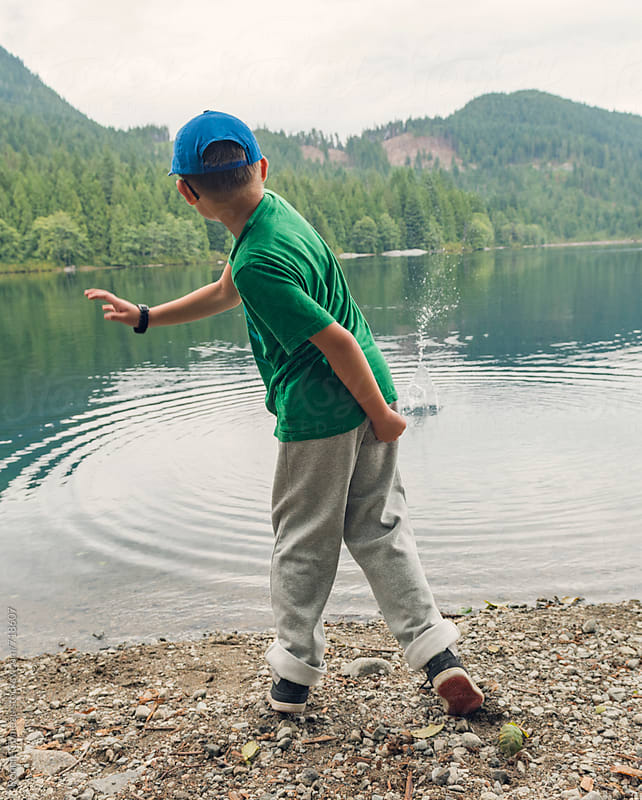 Boy Throwing Rock In Lake by Ronnie Comeau for Stocksy United