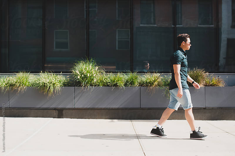 Young man walking on the sidewalk by Lauren Naefe for Stocksy United