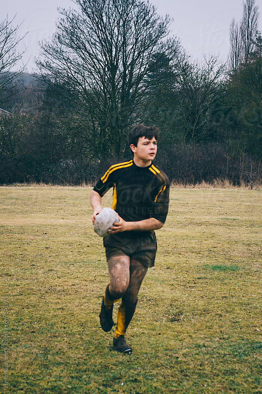 A teenage rugby player running with the ball by Helen Rushbrook for Stocksy United