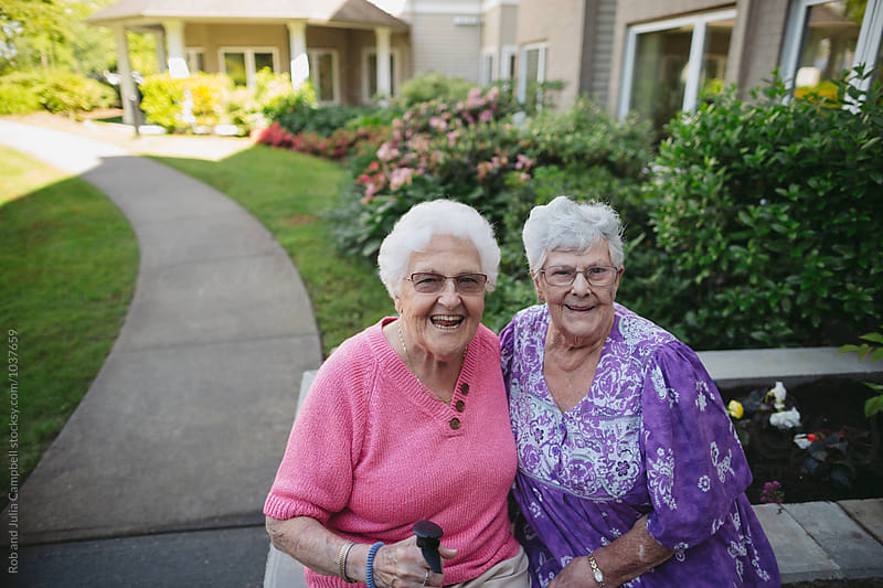 Two senior caucasian friends spending time together outside by Rob and Julia Campbell for Stocksy United