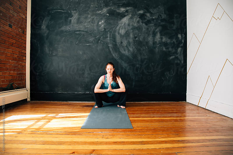 Woman in Prayer in Yoga Studio  by Abby Mortenson for Stocksy United