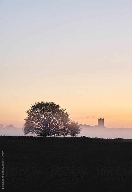 Rural church in fog at sunrise. Fakenham, Norfolk, UK. by Liam Grant for Stocksy United
