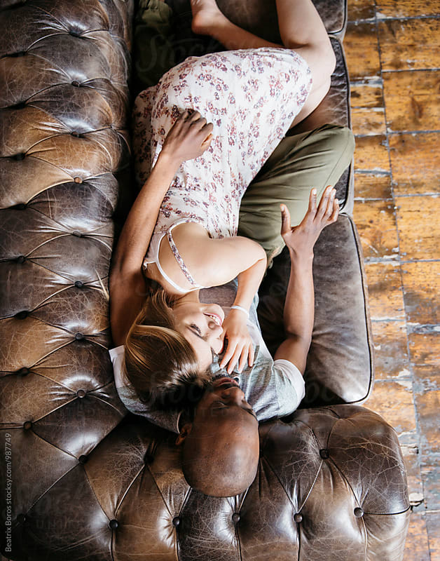 Overhead photo of a mixed race couple laying on the couch by Beatrix Boros for Stocksy United