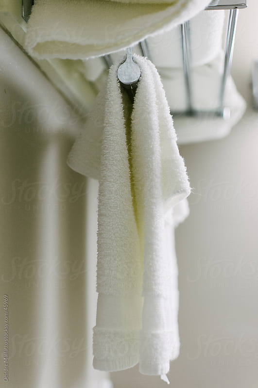 white bath towels hanging from a rack by Deirdre Malfatto for Stocksy United