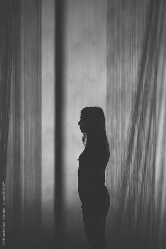 Silhouette of a woman standing alone among  the threads by Aleksandra Jankovic for Stocksy United