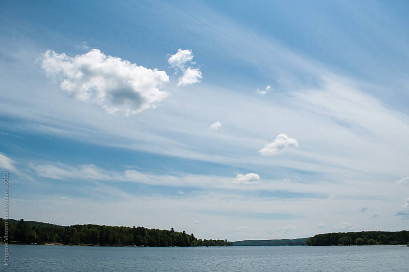 bands of clouds fill the sky over a freshwater lake by Margaret Vincent for Stocksy United