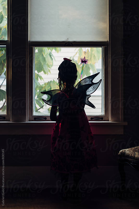 African American girl with fairy wings looking out the window by Gabriel (Gabi) Bucataru for Stocksy United