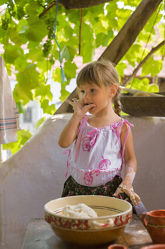 Little girl tasting homemade bread batter from her hand by RG&B Images for Stocksy United