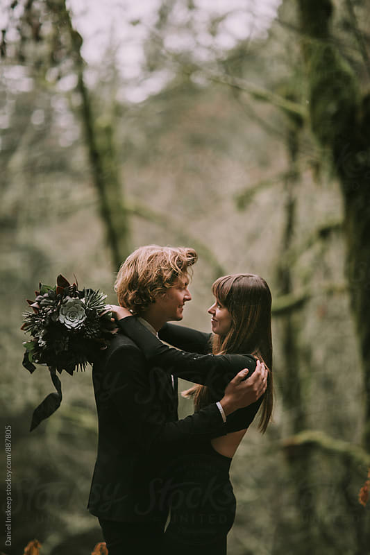 A Young Couple Embracing in the Woods by Daniel Inskeep for Stocksy United