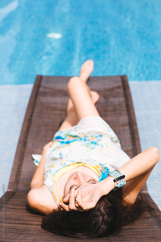 Young woman relaxing on sun lounger by michela ravasio for Stocksy United