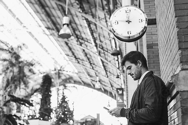 Businessman Using a Mobile Phone at the Train Station by Victor Torres for Stocksy United