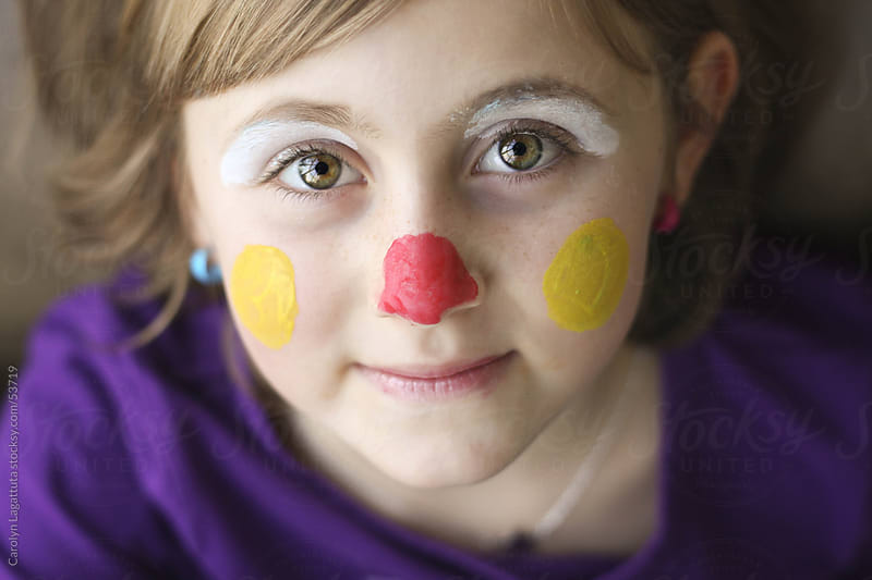 Cute little girl with paint on her face by Carolyn Lagattuta for Stocksy United