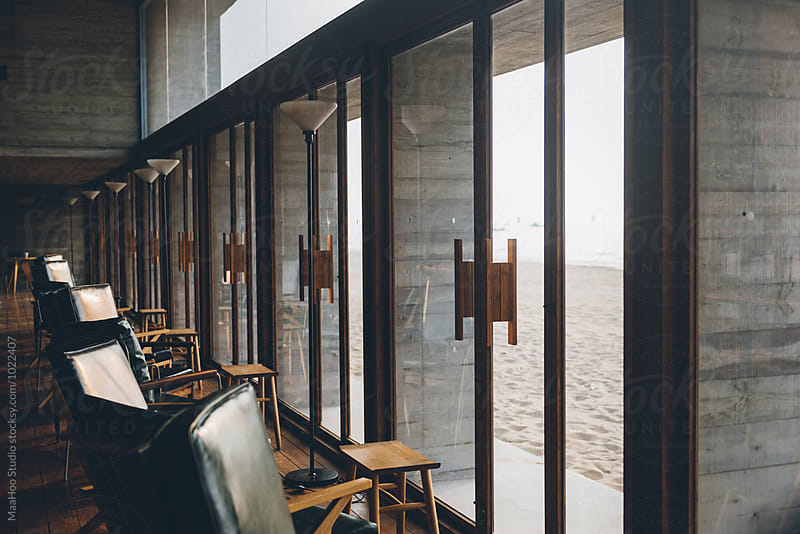 Chairs and tables in a building  along the seaside by MaaHoo Studio for Stocksy United