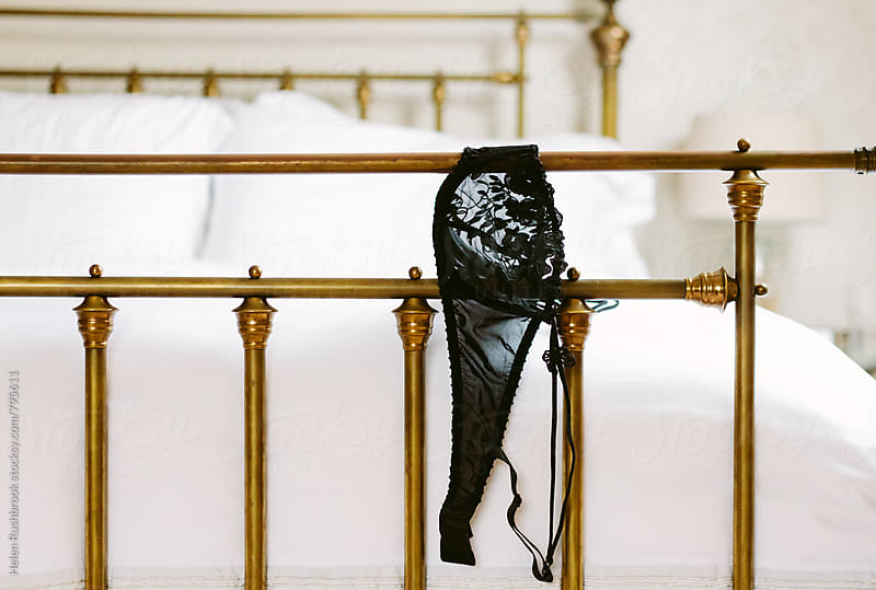 Black lingerie draped over the end of a metal bedstead by Helen Rushbrook for Stocksy United
