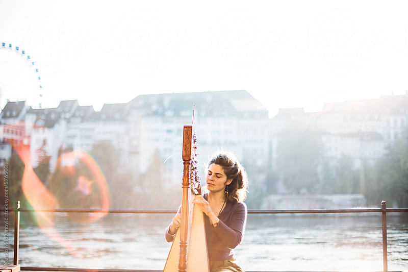 Woman playing harp on the streets of Basel by Marko Milovanović for Stocksy United
