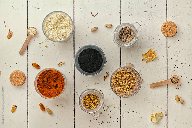 Colourful spices on a wooden table. by Marija Savic for Stocksy United