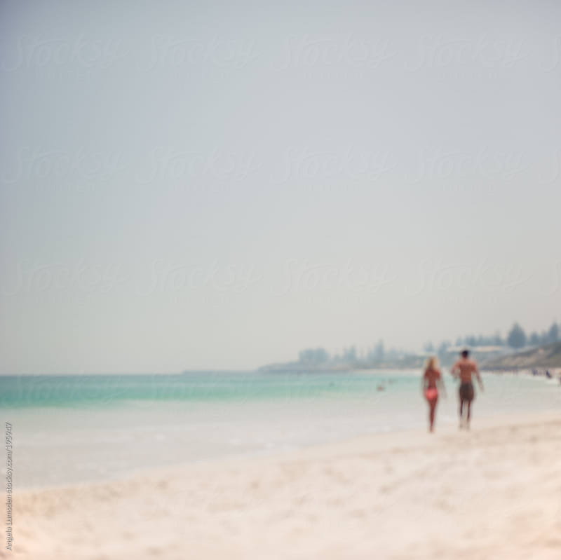 Blurred image of a couple walking on a beach on a hazy day by Angela Lumsden for Stocksy United