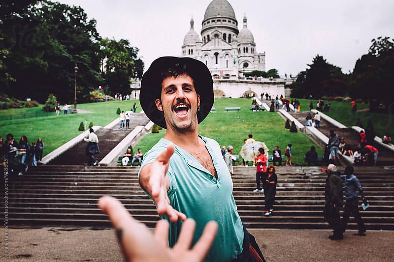 Young man having fun behind sacred heart church in Paris by Thais Ramos Varela for Stocksy United