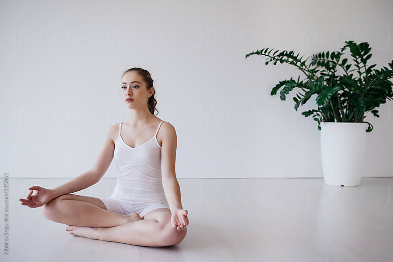 Young Woman Meditating in Lotus Pose by Alberto Bogo for Stocksy United