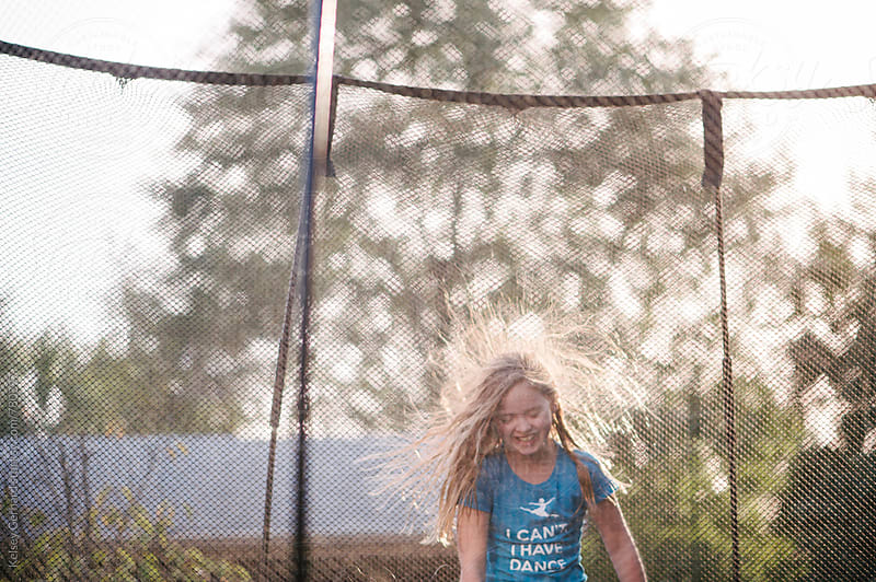 A young girl jumps on a trampoline with static in her hair. by Kelsey Gerhard for Stocksy United