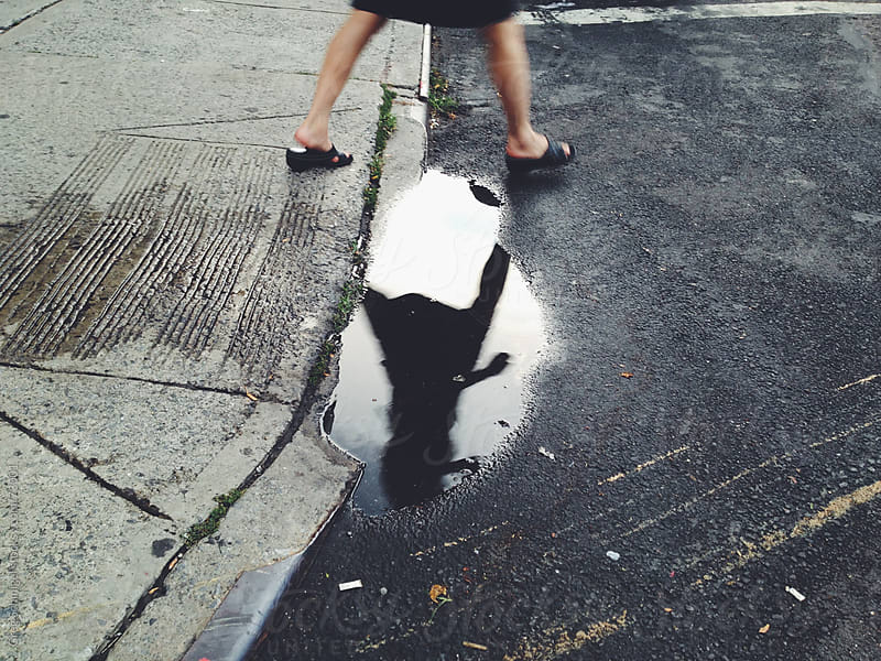 A person and their reflection walking over a rain puddle  by Greg Schmigel for Stocksy United