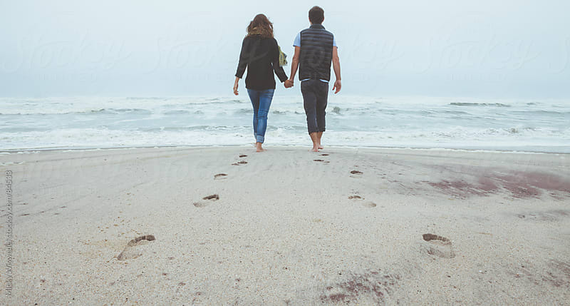 Couple holding hands walking on a beack by Micky Wiswedel for Stocksy United
