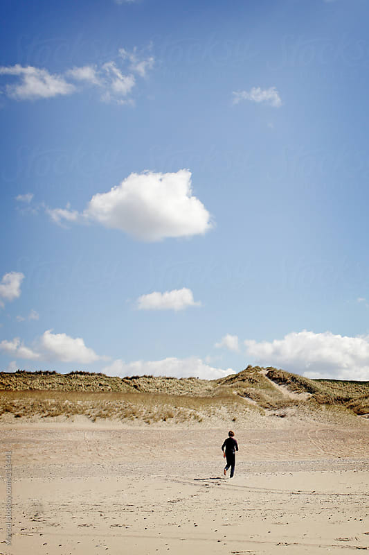 Boy running on a beach by Marcel for Stocksy United
