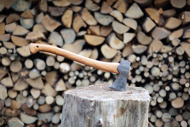 axe in a block of wood by Marcel for Stocksy United