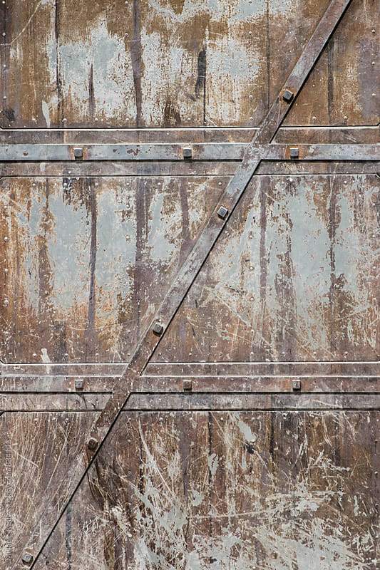 Detail of rusty metal door by Melanie Kintz for Stocksy United