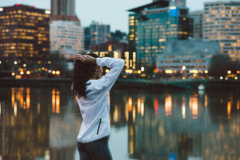 Young woman by the city waterfront during a night run. by Kate Daigneault for Stocksy United
