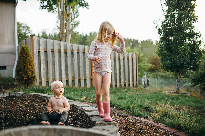 Young sister and Little Brother Play in the Garden by Amanda Voelker for Stocksy United