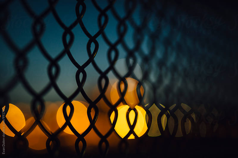 Chain Link Fence and Distant Lights at Dusk by Evan Dalen for Stocksy United