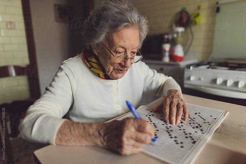 Old woman solving crossword puzzles in the kitchen by Silvia Cipriani for Stocksy United