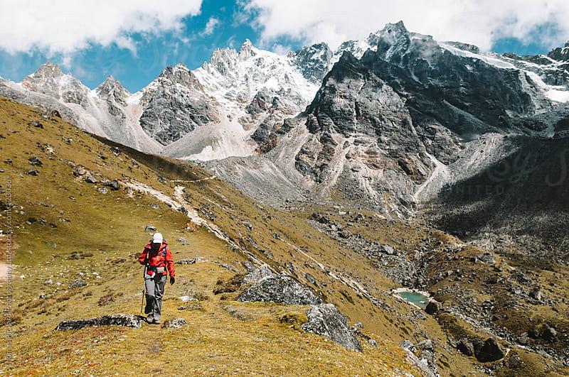 Female trekker descending from the mountains after crossing Renjo La Pass, Everest Region, Nepal. by Thomas Pickard for Stocksy United