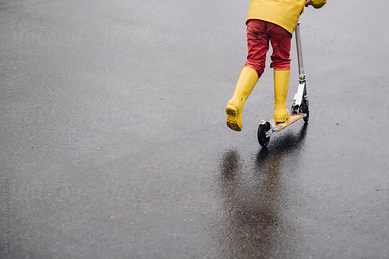 child with yellow boots on scooter by Léa Jones for Stocksy United