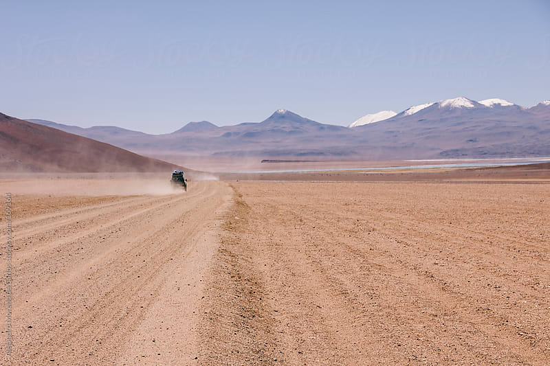 4wd car on desert driving offroad with mountains on background. Adventure travel in Bolivia by Alejandro Moreno de Carlos for Stocksy United