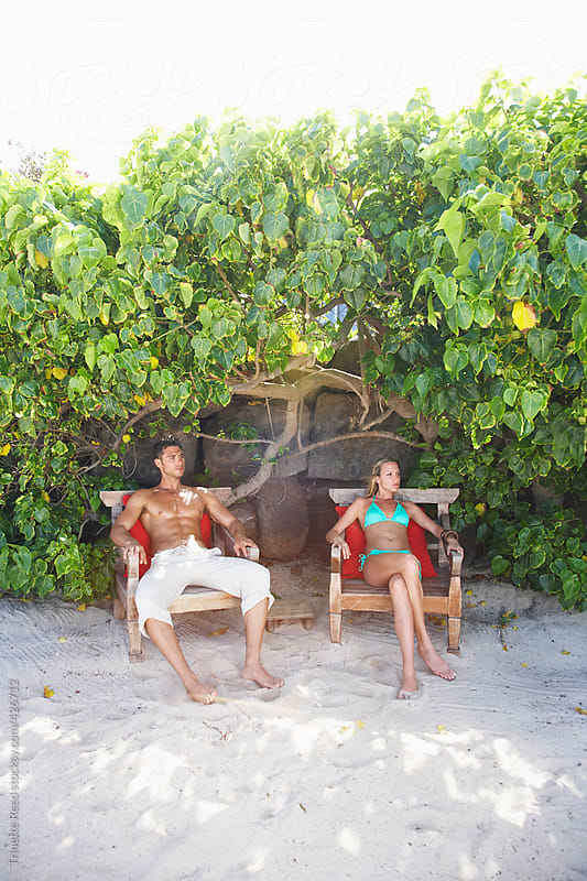 Couple relaxing on chairs on the beach at luxury resort by Trinette Reed for Stocksy United