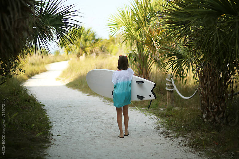 Girl Carrying Her Surfboard to the Beach by ALICIA BOCK for Stocksy United