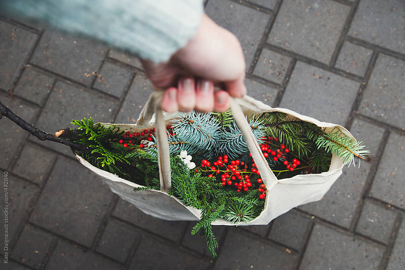 Hand holding large tote filled with hand picked wreath making supplies by Kate Daigneault for Stocksy United
