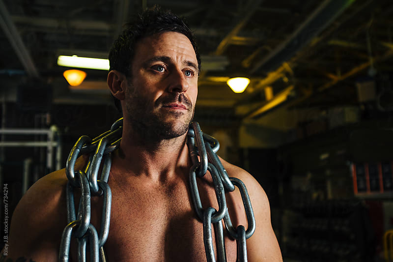 A shirtless muscular male draped in heavy chains. by Riley J.B. for Stocksy United