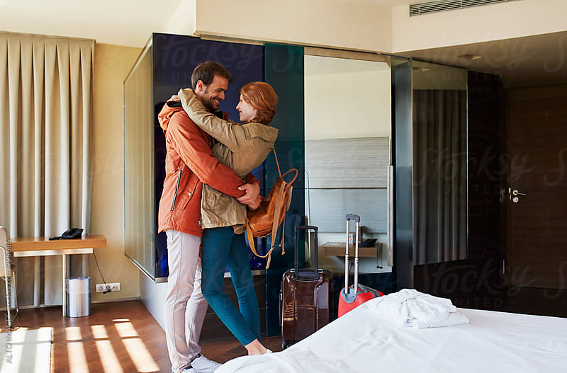 Happy Couple Embracing In Hotel Room by ALTO IMAGES for Stocksy United