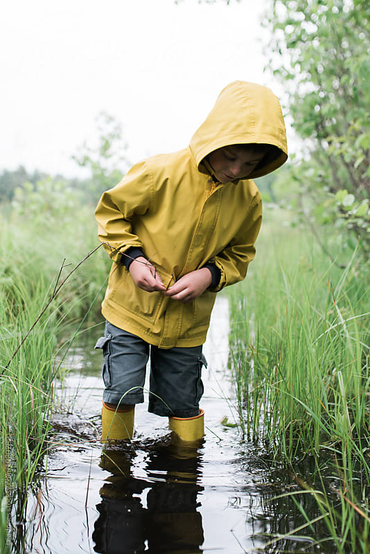 little boys walking in a flooded area by Léa Jones for Stocksy United