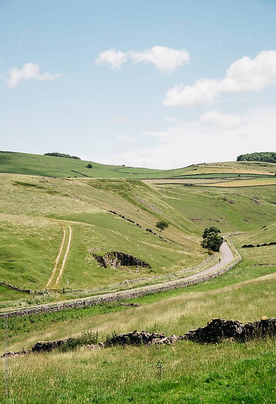 Cyclist on a remote road in the Derbyshire Dales. UK. by Liam Grant for Stocksy United