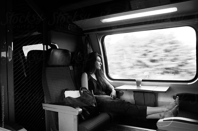 A film portrait of young beautiful woman seating at the train by Anna Malgina for Stocksy United